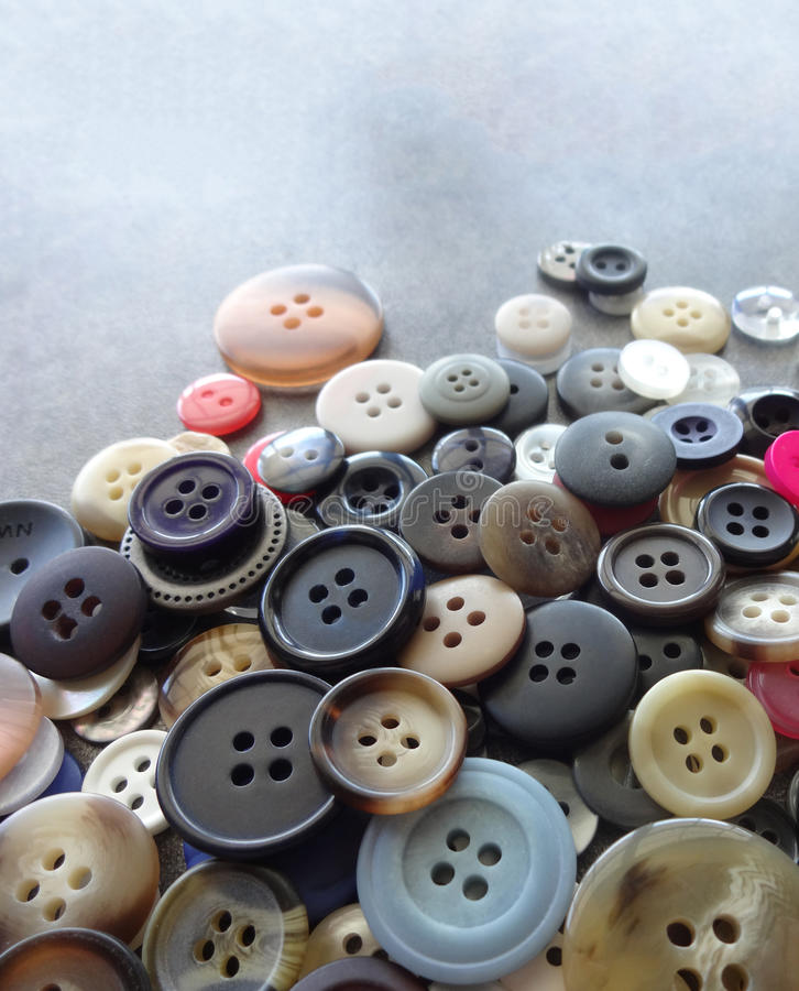 Sewing Buttons Background. Various Sizes and Colors of Sewing Buttons against a Gray Background stock images