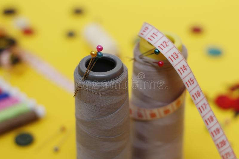 Sewing buttons and threads on a yellow background. Needlework concept. A lot of multi-colored little bobbins of sewing thread on a yellow background. Skeins of royalty free stock images