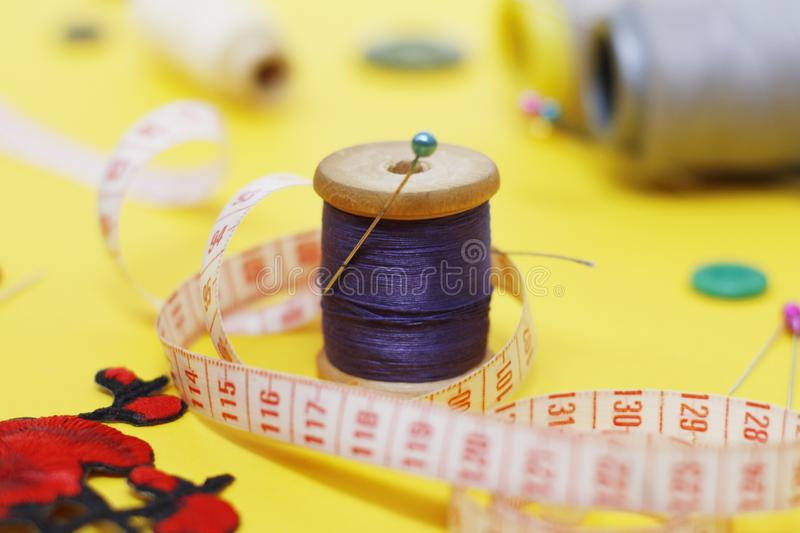 Sewing buttons and threads on a yellow background. Needlework concept. A lot of multi-colored little bobbins of sewing thread on a yellow background. Skeins of stock image
