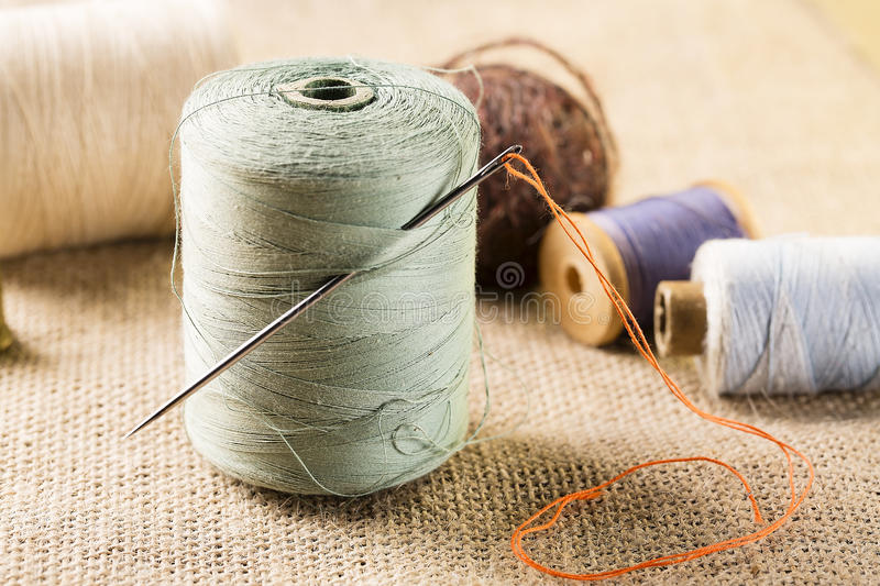 Sewing concept. Thread spool with needle with other spools on canvas background.  stock photo