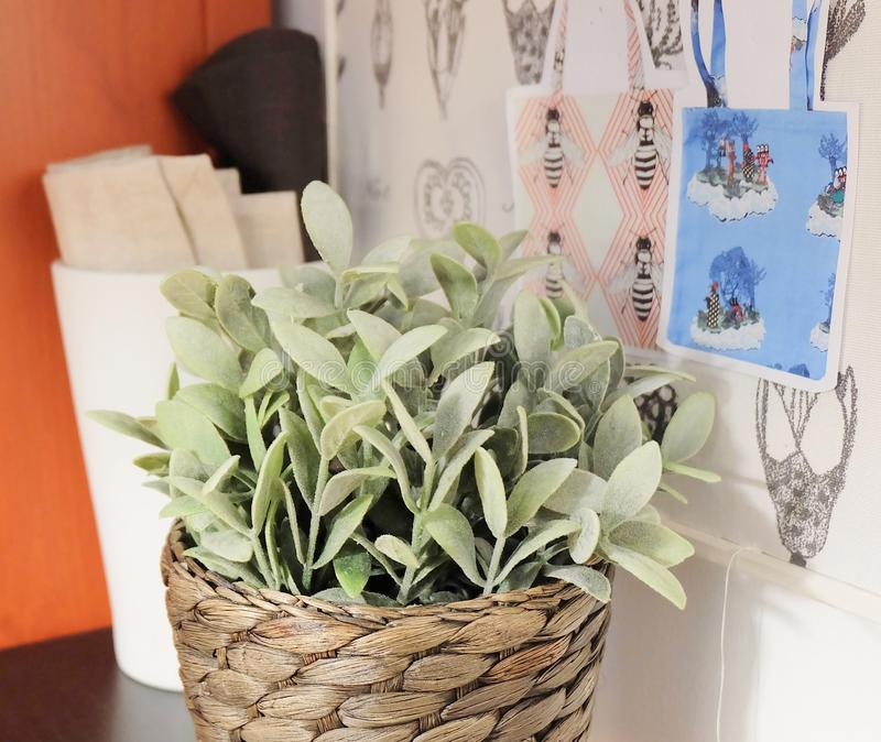 Fabric Rolls with Artificial Plants in Sewing Room. Sewing and Crafting Room with Fabric Rolls, Craft Board and Artificial Green Plant stock photo