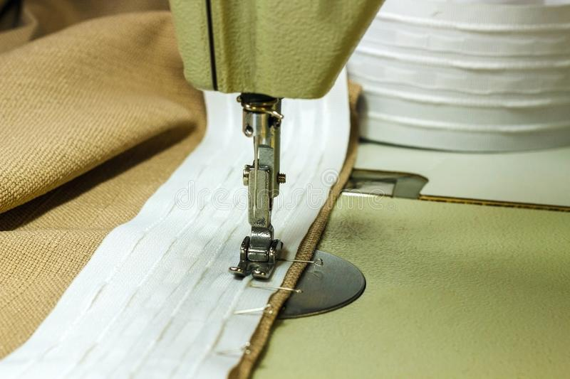 Sewing curtain tape with a sewing machine, close-up royalty free stock photo