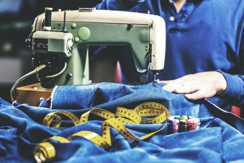 Sewing denim jeans with sewing machine. Repair jeans by sewing machine. Alteration jeans, hemming a pair of jeans, handmade. Garment industrial concept stock images