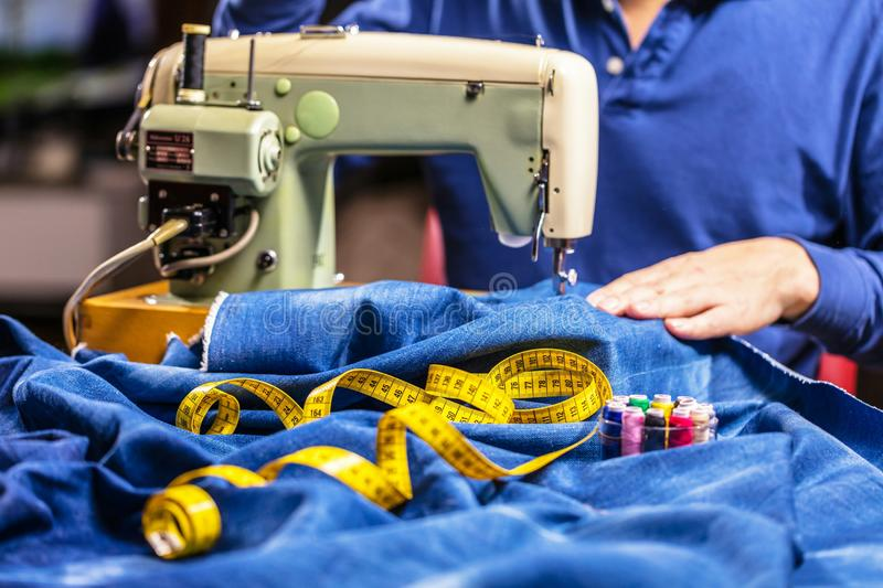 Sewing denim jeans with sewing machine. Repair jeans by sewing machine. Alteration jeans, hemming a pair of jeans, handmade. Garment industrial concept royalty free stock photography