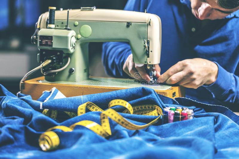 Sewing denim jeans with sewing machine. Repair jeans by sewing machine. Alteration jeans, hemming a pair of jeans, handmade. Garment industrial concept stock photography