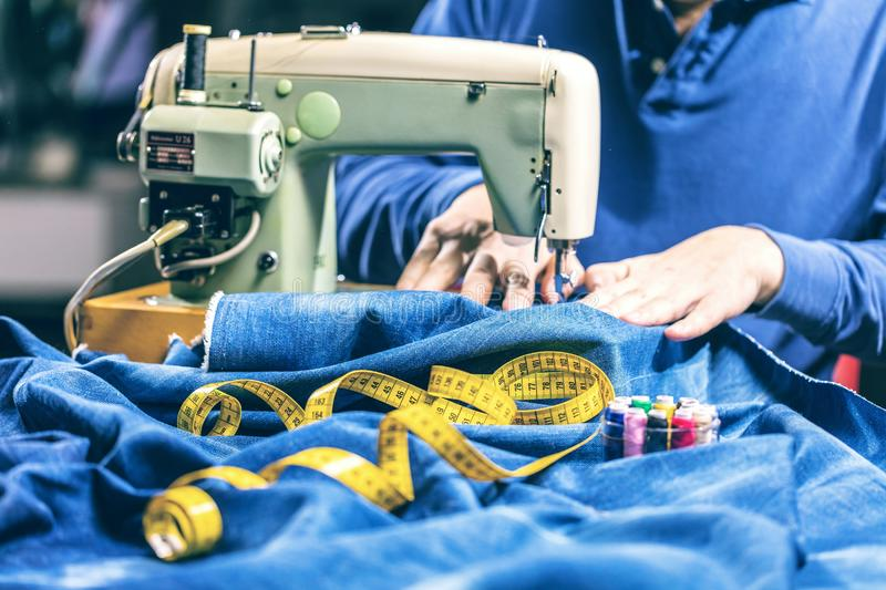 Sewing denim jeans with sewing machine. Repair jeans by sewing machine. Alteration jeans, hemming a pair of jeans, handmade. Garment industrial concept royalty free stock images