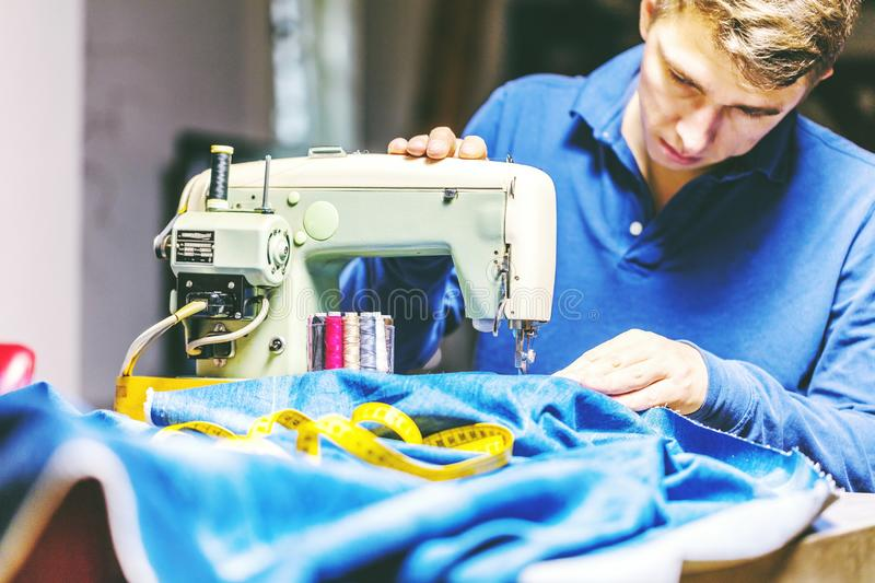 Sewing denim jeans with sewing machine. Repair jeans by sewing machine. Alteration jeans, hemming a pair of jeans, handmade. Garment industrial concept royalty free stock image