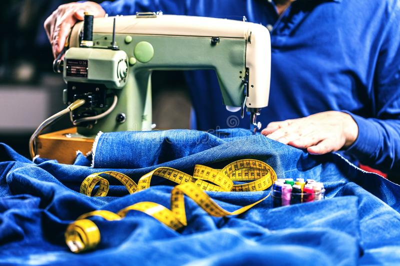 Sewing denim jeans with sewing machine. Repair jeans by sewing machine. Alteration jeans, hemming a pair of jeans, handmade. Garment industrial concept stock photos