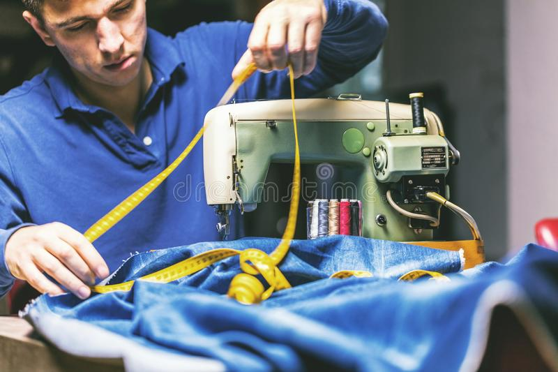 Sewing denim jeans with sewing machine. Repair jeans by sewing machine. Alteration jeans, hemming a pair of jeans, handmade. Garment industrial concept stock photo
