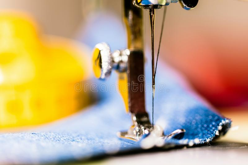 Sewing denim jeans with sewing machine. Repair jeans by sewing machine. Alteration jeans, hemming a pair of jeans, handmade. Garment industrial concept royalty free stock photo