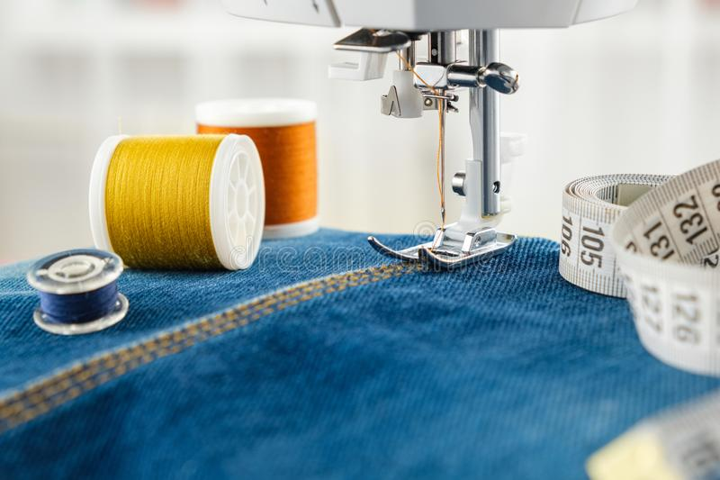 Close up of needle of sewing machine on the denim fabric stitch, threads and measuring tape stock photos
