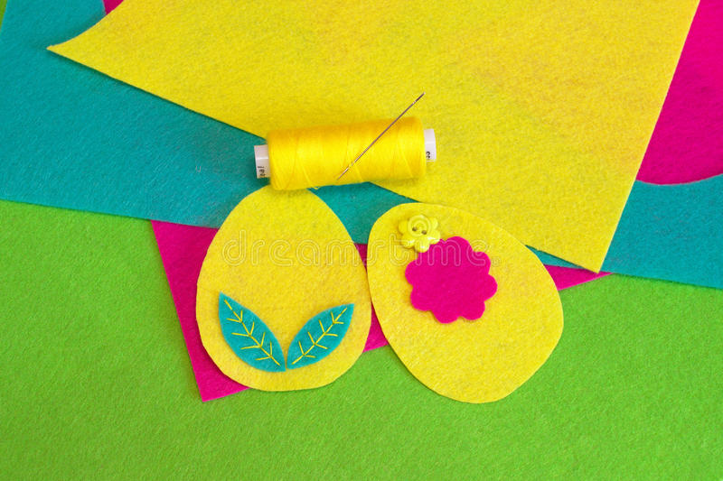 Sewing the felt Easter eggs with flower. Colored thread. Colorful felt leaves set, flower button. Sewing concept. Sewing set for felt Easter egg - how to make royalty free stock photos