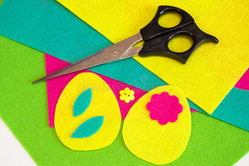 Sewing the felt Easter eggs with flower. Colorful felt leaves set. Flower button, scissors. Sewing concept. Sewing set for felt Easter egg - how to make handmade stock photos