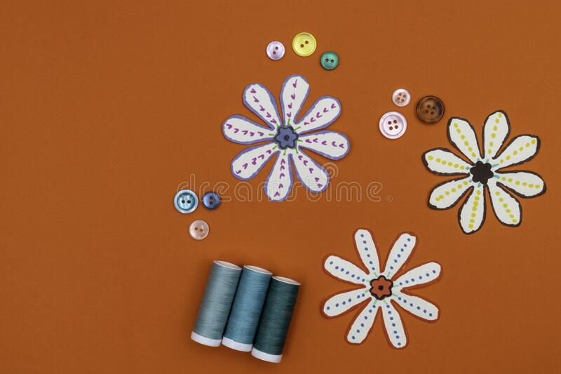 Sewing concept with sewing buttons and threads on a orange background royalty free stock photography