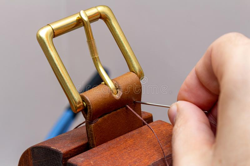 Sewing handmade brown leather belt with hands needle thread.  stock photos