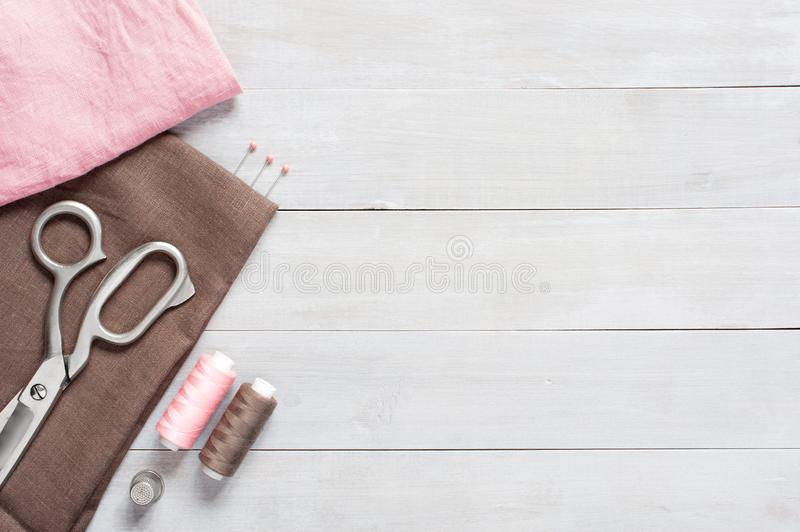 Sewing items and linen fabric on the table. Sewing items and linen fabric on the light wooden table, wooden background stock photos