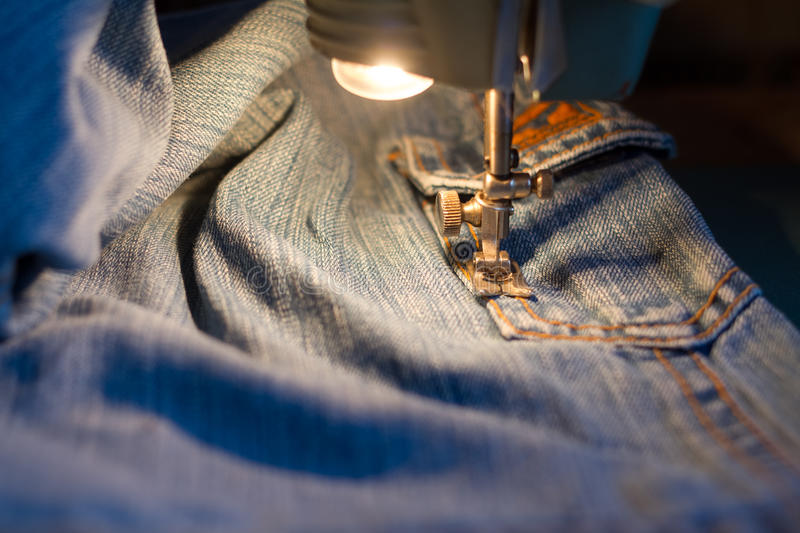Sewing jeans. Sewing jeans on the sewing machine royalty free stock photo