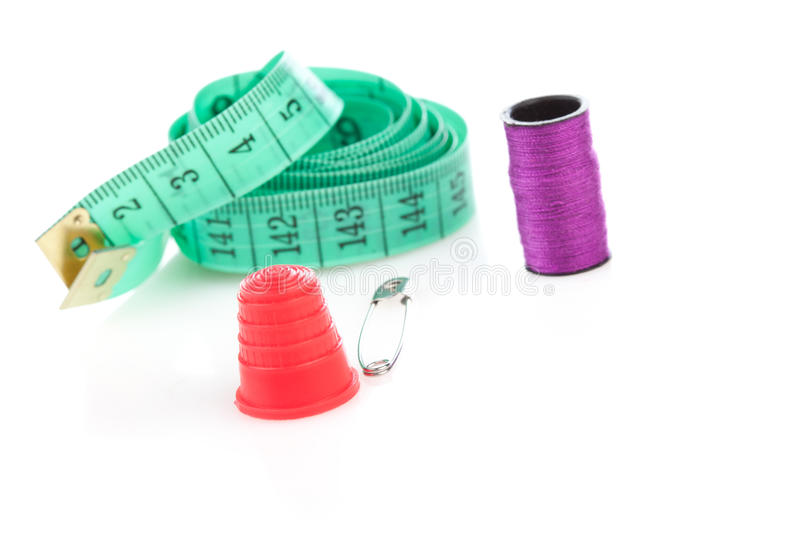 Sewing kit with accessories. Including a coiled blue tape measure, thimble, reel of cotton and safety pin royalty free stock photos