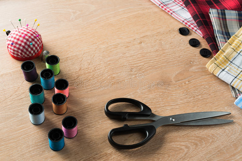 Sewing kit on table. Old scissors bobbins threads material on wooden table royalty free stock image