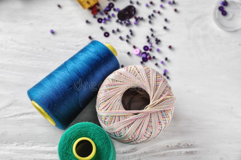 Sewing and knitting threads on white wooden background royalty free stock images