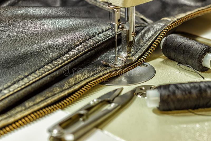 Sewing leather jacket repairing leather jacket scissors, thread, sewing machine, close-up stock photos