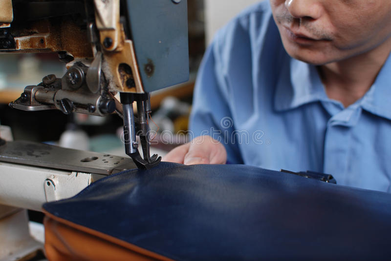 Sewing leather materials. The worker sewing leather materials in the factory stock photos