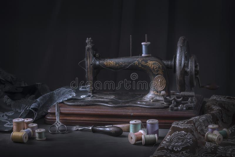 The sewing machine and accessories - threads, needle, scissors, measuring tape. stock photography