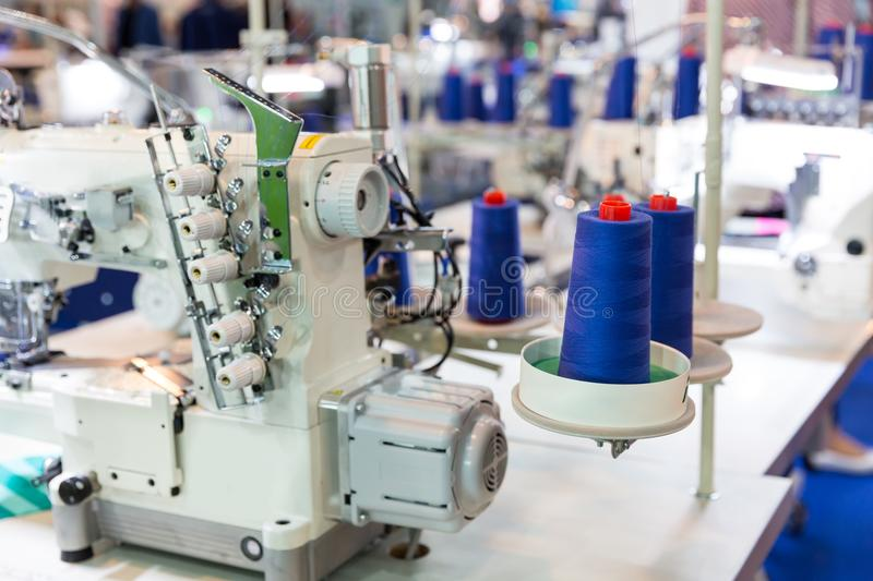 Sewing machine and cloth, nobody, clothing factory. Fabric production, sew manufacturing, needlework technology stock photo