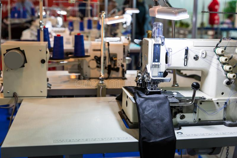 Sewing machine on leather cloth factory, nobody. Sewing machine in cutting shop on leather cloth factory, nobody. Fabric production, sew manufacturing stock images