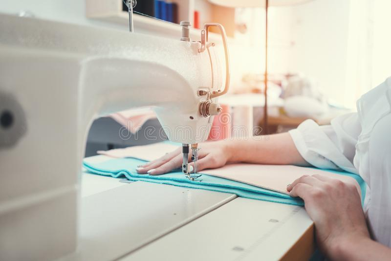 Sewing machine and female hands of close up view. Young dressmaker sew and working with cloth in design studio stock image