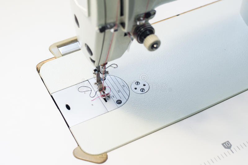 Sewing machine foot. On material with threaded needle ready to sew. Operator`s hand on material in top left corner stock photography
