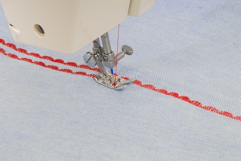 A sewing-machine makes figure seam. stock photo