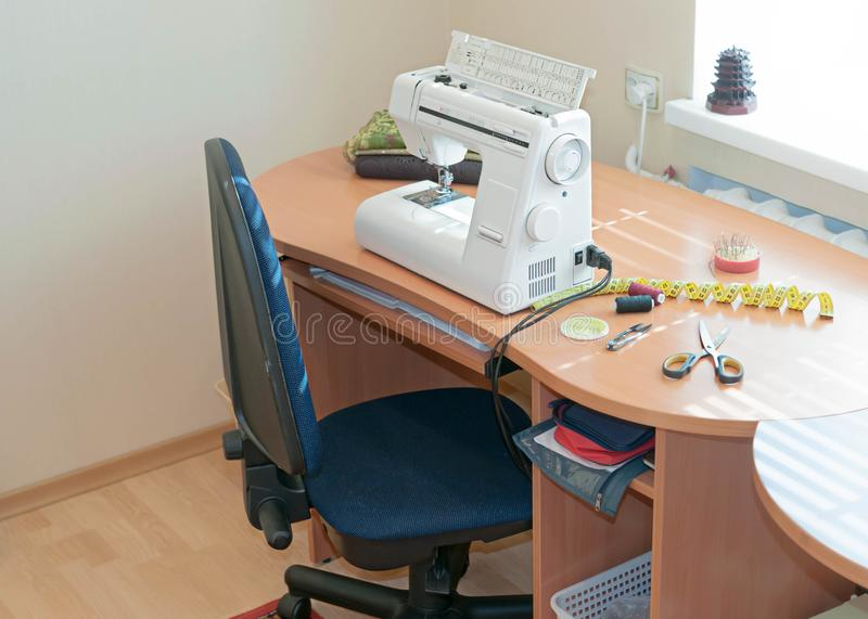 Sewing machine, measuring tape, spools of thread and scissors on wooden table royalty free stock photo