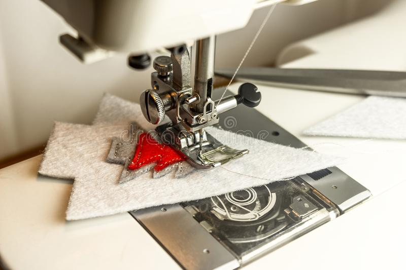 Sewing machine in the process of sewing felt with silver threads. Sewing machine in the process of sewing parts with silver threads stock photography