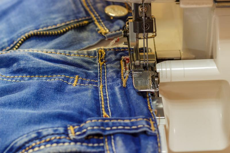 Sewing machine repair jeans trousers, close-up royalty free stock photo