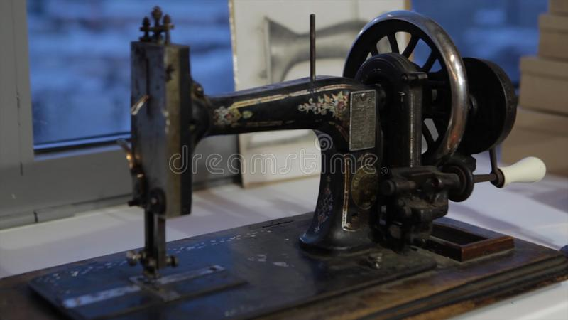 Sewing machine, seamstress sewing at machine and women`s hands. Antique Sewing Machine Franklin. Young Woman Wears. Protective Face Mask Working On Sewing stock photos