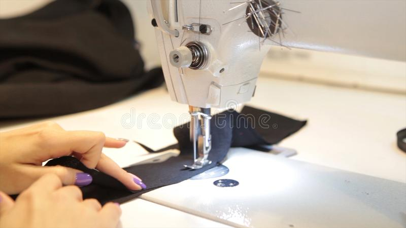 Sewing machine, seamstress sewing at machine and women`s hands. Antique Sewing Machine Franklin. Young Woman Wears. Protective Face Mask Working On Sewing stock photo