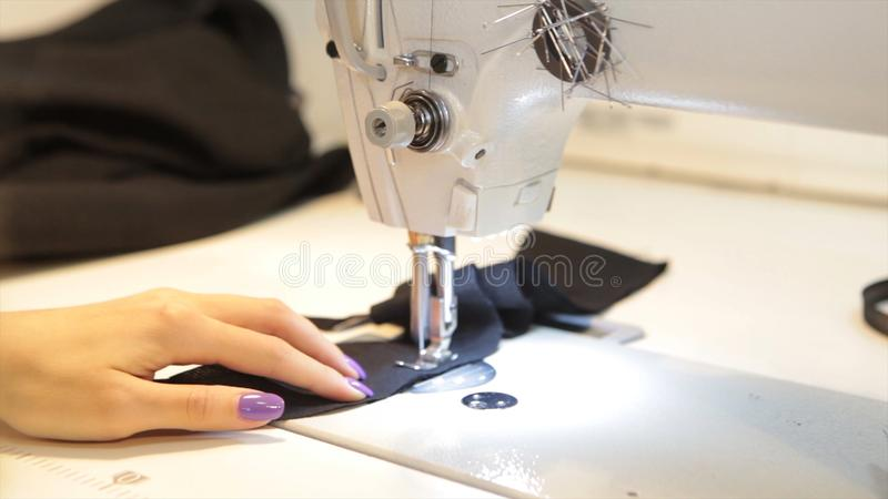 Sewing machine, seamstress sewing at machine and women`s hands. Antique Sewing Machine Franklin. Young Woman Wears. Protective Face Mask Working On Sewing stock photography