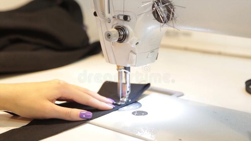 Sewing machine, seamstress sewing at machine and women`s hands. Antique Sewing Machine Franklin. Young Woman Wears. Protective Face Mask Working On Sewing royalty free stock photos