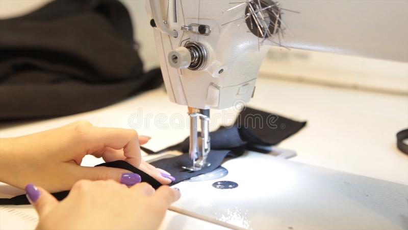 Sewing machine, seamstress sewing at machine and women`s hands. Antique Sewing Machine Franklin. Young Woman Wears. Protective Face Mask Working On Sewing royalty free stock photo