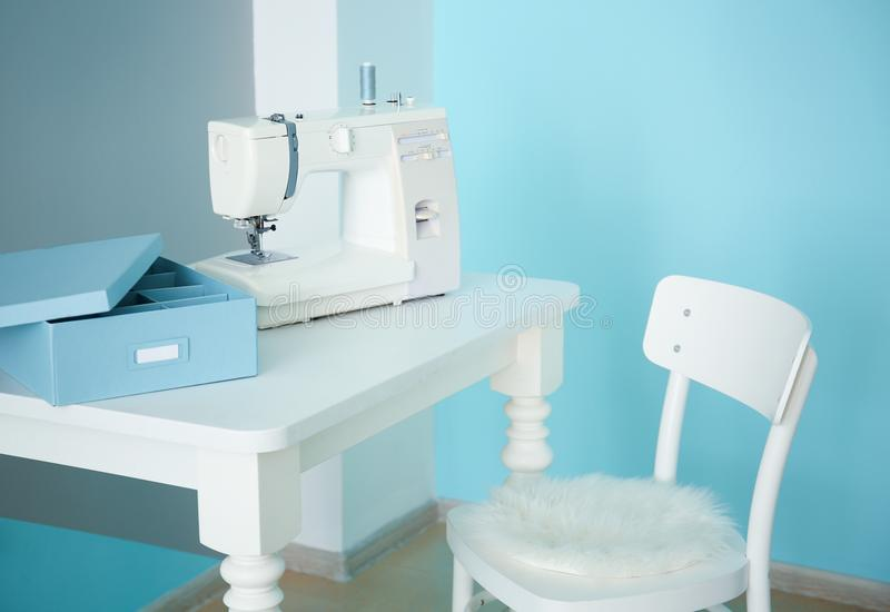 Sewing machine on table in workshop. Sewing machine on table in tailor`s workshop stock images