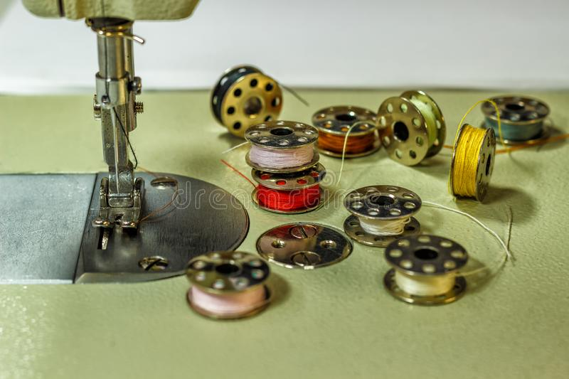 Sewing machine, on the table of which lie bobbins with multi-colored threads stock photo