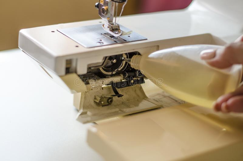 Sewing machine. Work by the light of the built-in hardware lamp. Steel needle with looper and presser foot close-up stock image