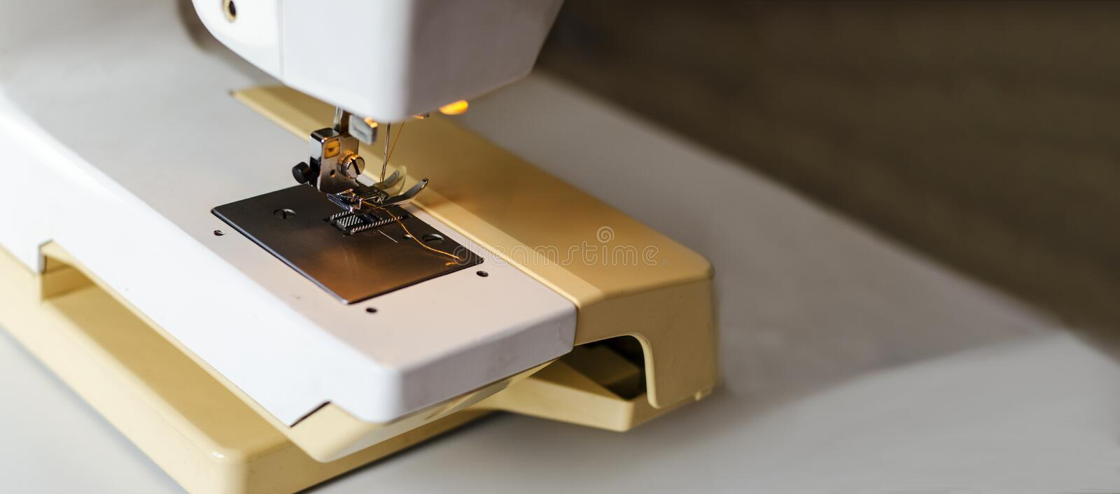 Sewing machine. Work by the light of the built-in hardware lamp. Steel needle with looper and presser foot close-up stock photography
