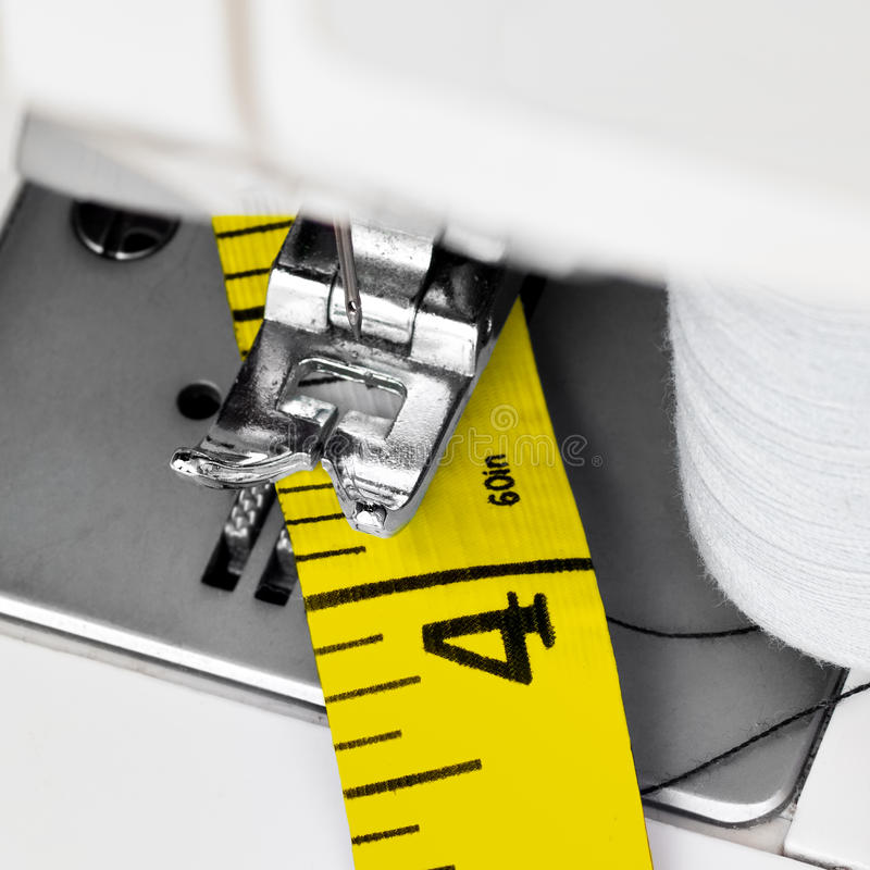 Sewing machine and yellow measuring tape stock photography