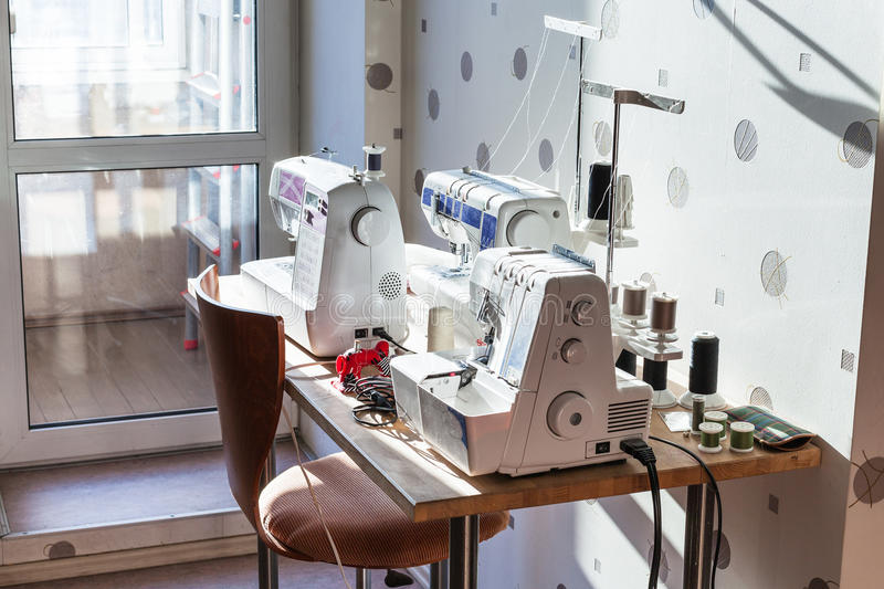 Sewing machines and serger on table stock photo