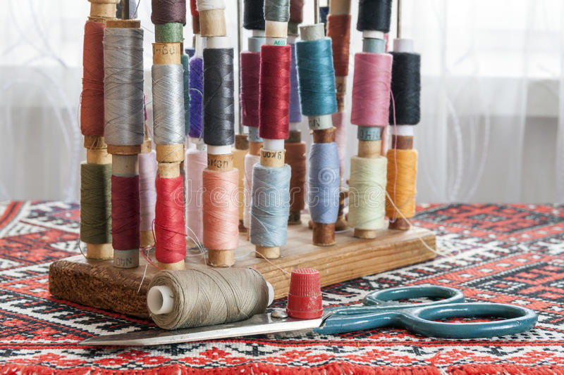 Sewing multicolored threads of soft pastel vintage colors on spools. Sewing tailor related accessories. royalty free stock photos