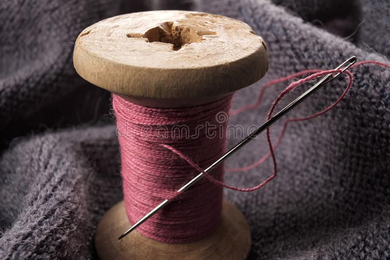 Sewing needle and cotton thread on wooden spool macro view. royalty free stock photo