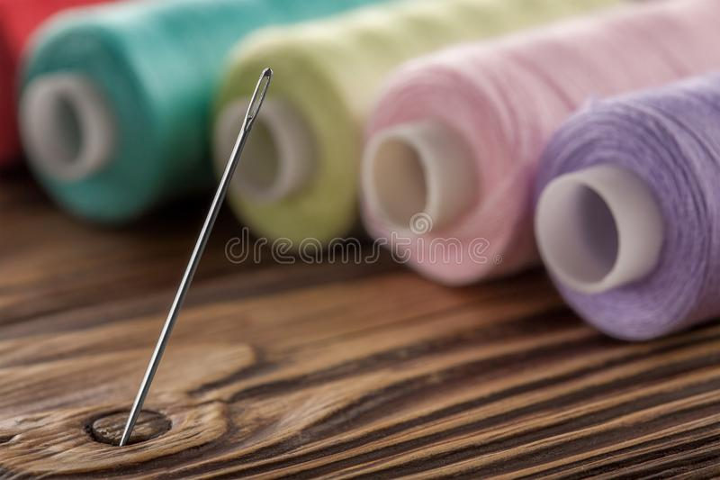 Sewing needle on a wooden background in thread stock images