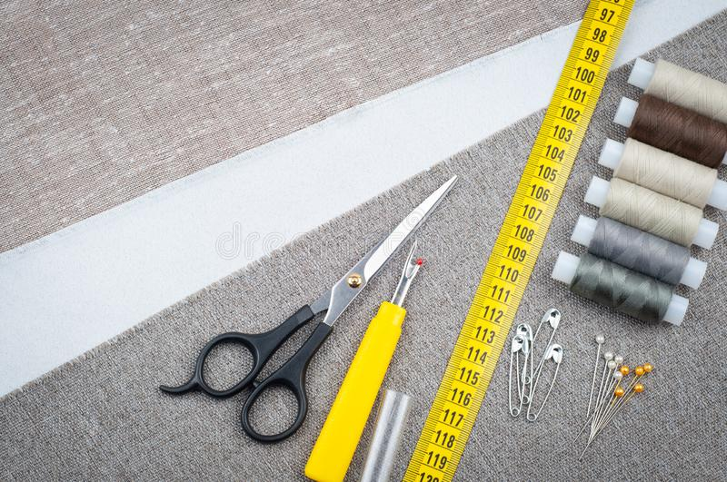 Sewing pattern composition with scissors, spools of thread, pins, measuring tape royalty free stock images